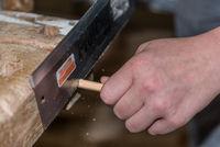 Schreiner sägt mit einer Handsäge Holzdübel - Nahaufnahme