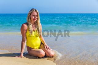 Pretty dutch girl sitting on beach near sea