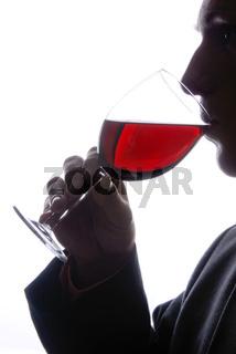 Junger Mann trinkt ein Glas Wein