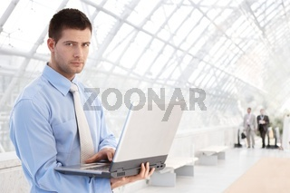 Young businessman using laptop at passage