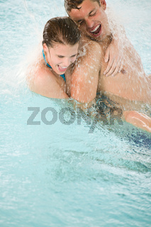 Young happy couple have fun under water stream in pool