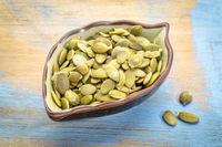 raw pumpkin seeds in a leaf bowl