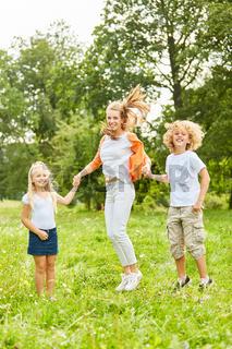Mutter spielt und hüpft mit ihren Kindern