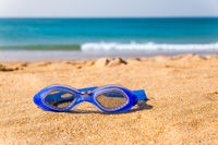 Blue swimming goggles lying at beach with sea