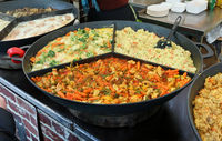 Fast street food - rice, boiled on couple, and other stewed vegetables on big iron frying pan.