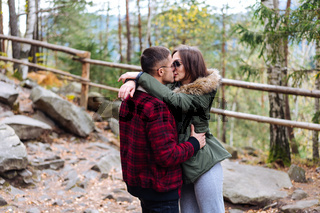 girl and a young man kissing in the woods