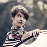 Happy young fashion woman in striped tank top leaning on her car