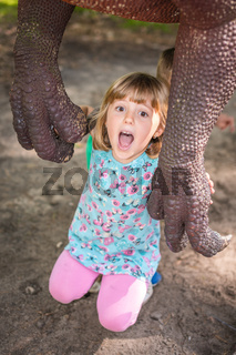 Little girls under the claws of a dinosaur
