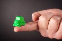 Finger mit kleinem grünem Auto