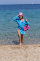 Young tourist girl emerges from the Aegean Sea on the coast of Sithonia Peninsula