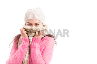 Young woman wearing knitted scarf and hat covering her mouth