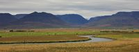 River, green meadow and mountains near Saudarkrokur, Iceland. Cloudy late summer day.