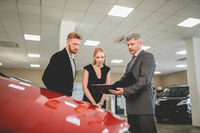 Auto dealer agent showing documents with car specifications to buyers.