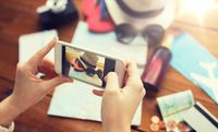 close up of woman with smartphone and travel stuff