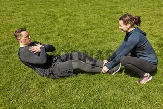 Mann macht Sit-Ups mit Personal Trainer