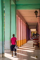 Cuban man walking through colorful passway in Havana