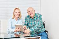 Neugieriger Senior und junge Frau mit Tablet