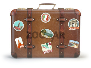 Vintage suitcase with travel stickers isolated on white background.