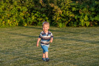 One year old baby boy running on meadow