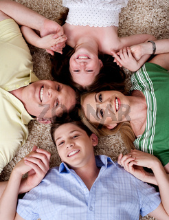 Happy family of four lying on the carpet and holding each others hand