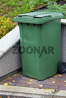 Green plastic standard garbage container installed near the village house