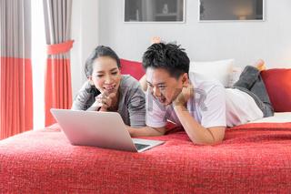 Couples using laptop bedroom