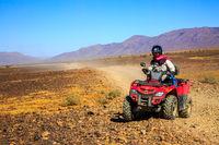 Ait Saoun, Morocco - February 22, 2016: Man riding quad bike on sand