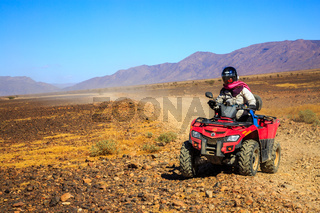 Ait Saoun, Morocco - February 22, 2016: Man riding quad bike on sand