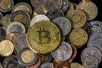 Golden bitcoin over a pile of coins.