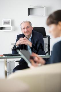 Älterer Mann als Geschäftsführer in einem Meeting