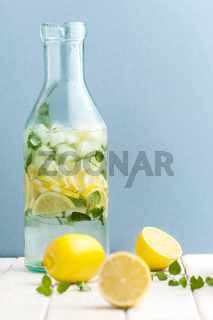 Bottle with cold refreshing lemonade on a blue background.