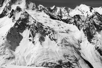 Black and white snow covered mountains with glacier at cold sun day