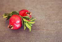Two pomegranate fruits with leaves on textile background