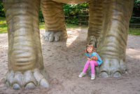 Cute little girl under huge diplodocus dinosaur