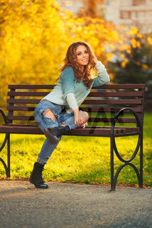 Happy young fashion woman with long curly hairs sitting on bench in city park
