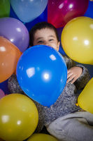 Fun, Brunette boy playing with a lot of colorful balloons, smiles and joy at birthday party