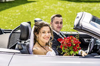 Bridal couple with wedding car