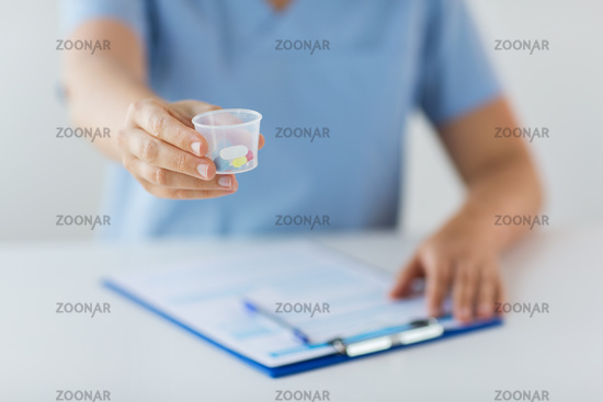 close up of doctor with pills in medical cup