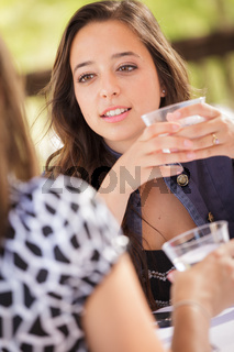 Expressive Young Adult Woman Having Drinks and Talking with Her Friend Outdoors