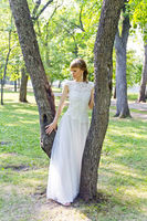 Bride in white lace dress standing near tree