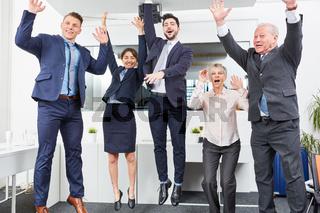 Business Team springt und jubelt im Büro