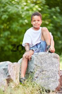 Afrikanischer Junge sitzt entspannt auf einem Stein