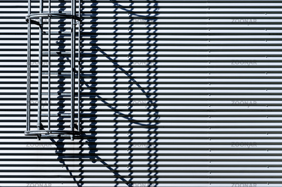 Corrugated metal wall with fire escape ladder.
