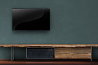 led tv on dark green with wooden media furniture