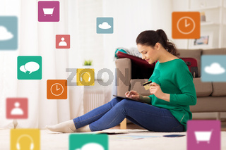 woman with tablet pc and credit card at home