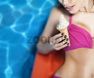 Closeup of young woman in bikini with ice cream relaxing in swimming pool.