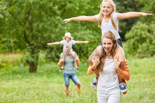 Glückliche Kinder reiten huckepack
