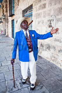 Havana, Cuba - December 12, 2016:  Traditional Cuban man with walking cane posing for photos while smoking big cuban cigar in Old Havana, Cuba.