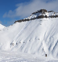 Skiers and snowy slope for freeride with traces of skis, snowboards and avalanches