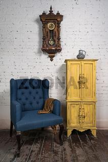 Vintage blue armchair, yellow cupboard, pendulum clock and orange scarf